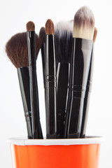 Cosmetic brushes in orange cup