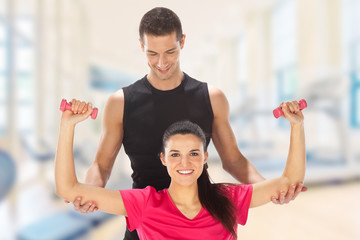 Woman with her personal trainer exercising with weights in gym