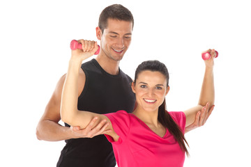 Woman with her personal fitness trainer exercising with weights