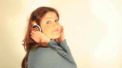 Music. Woman listening to music on headphones enjoying a dance