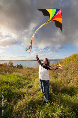 Boy in autumn playing with kite