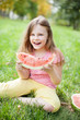 little girl on green grass eating watermelon