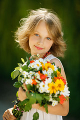 Smiling girl with bunch of wildflowers standing outdoors