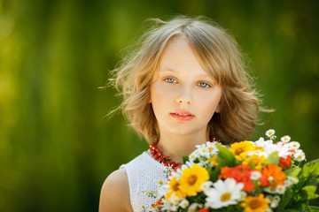 Girl with bunch of flowers standing outdoors