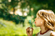 Portrait of funny lovely girl blowing soap bubbles outdoor