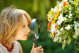 Girl exploring flowers through the magnifying glass outdoors