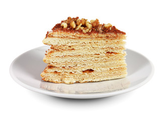 Piece of cake with nuts and chocolate crumbs on white plate