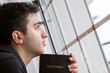 Man Holding Bible Looking Out Window