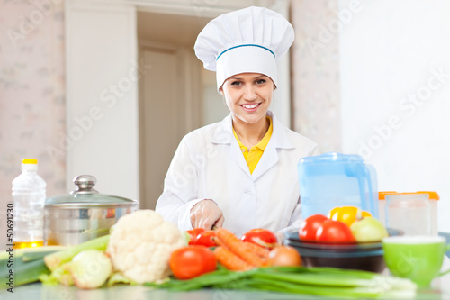 cook woman  in uniform cutting vegetables