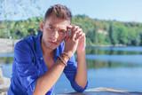 man posing at table near lake