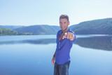 man pointing near the lake