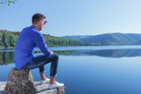 man sits by the lake & looks away