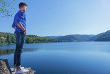 casual man stands near lake
