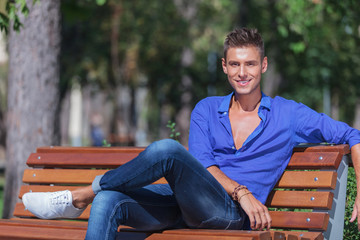 man posing on bench in park