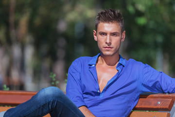 young man poses on bench