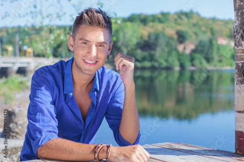 man at table near lake