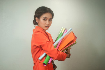 Busy Asian business woman with a folders and colorful papers.