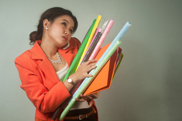 Busy Asian business woman with a folders and colorful paper.