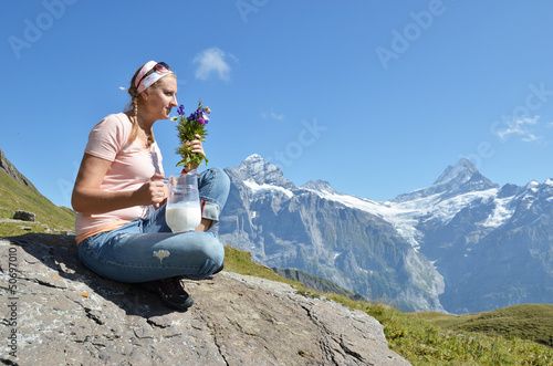 Girl holding a jug of milk and flowers against Swiss Alps