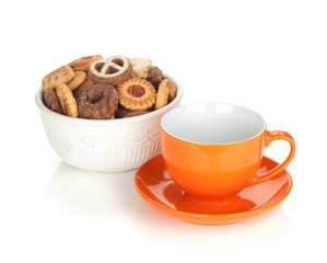 Various cookies in bowl and orange tea cup