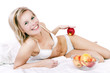 Bed of a beautiful blond woman holding apple.