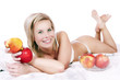 Cheerful girl in bed surrounded by apples.