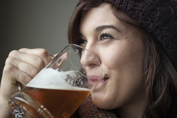Beautiful Young Woman in Knitted Scarf and Hat Drinks Beer