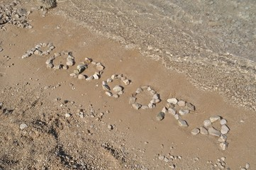 The Podgora word spelled out with pebbles on beach of Podgora