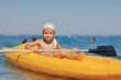 little boy swimming in the yellow boat on the sea