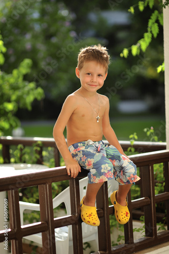 wonderful emotional little boy sitting on a fence in the open ai