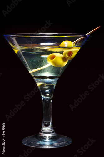 Glass of Martini with olives on black