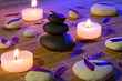 white and black stones, purple petals, and candles on bamboo