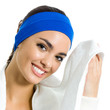 Cheerful woman in fitness wear with towel, over white