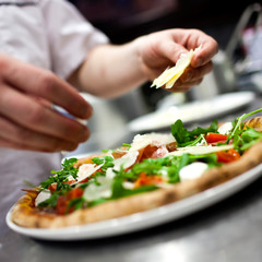 Closeup hand of chef baker in white uniform making pizza at kitc