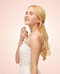 girl spraying pefrume on her neck