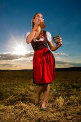 Frau trinkt Bier und hält Brezel in Bayern Tracht