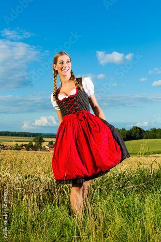 Junge Frau auf der Wiese und trägt Dirndl