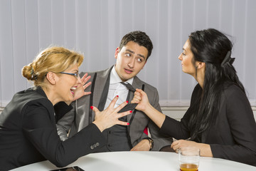 Angry businesswomen harassing their guilty business partner