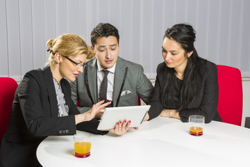 Group of three business people discussing and planning in office