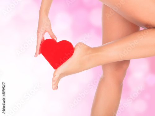 Female legs against a pink background with blurred lights