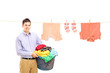 Smiling guy holding a laundry bin and a laundry line with clothe