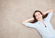 Attraktive junge Frau liegt entspannt auf dem Teppichboden