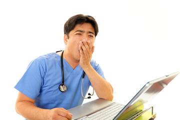 あくびをする医師