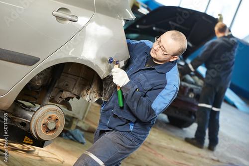 Leinwanddruck Bild auto repair man flatten metal body car