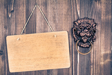 Lion head door knocker and sign board on wood background