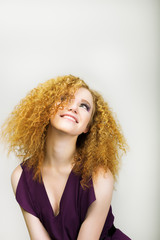 Happy Woman with Curly Golden Hairs smiling. Positive Emotions