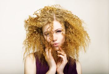 Embarrassment. Shaggy Red-Haired Curly woman grimacing