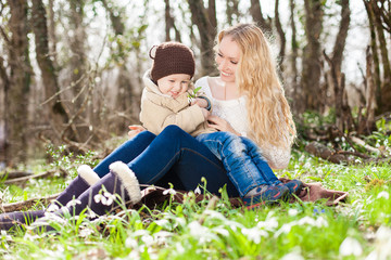 Smiling mother and little son on grass and snowdrops