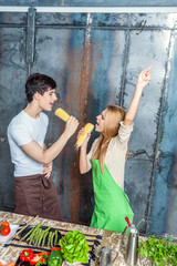 Young Funny Couple Playing with Corn Cobs
