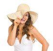 Smiling young woman in swimsuit playing with hat